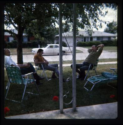 Men sitting in lawn chairs on front yard