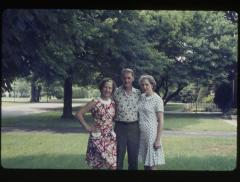 Two women and a man standing outdoors