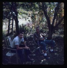 Two men sitting under trees