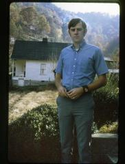 Man standing outdoors with a white house in the background