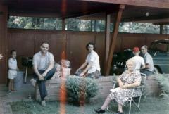 Family sitting under a carport