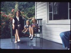 Woman and two children on porch bench