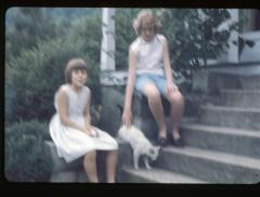 Two girls with a cat sitting on the front steps of a house