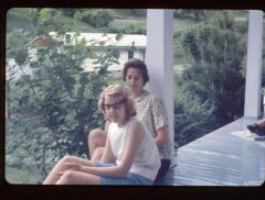 Woman and young girl sitting on a porch