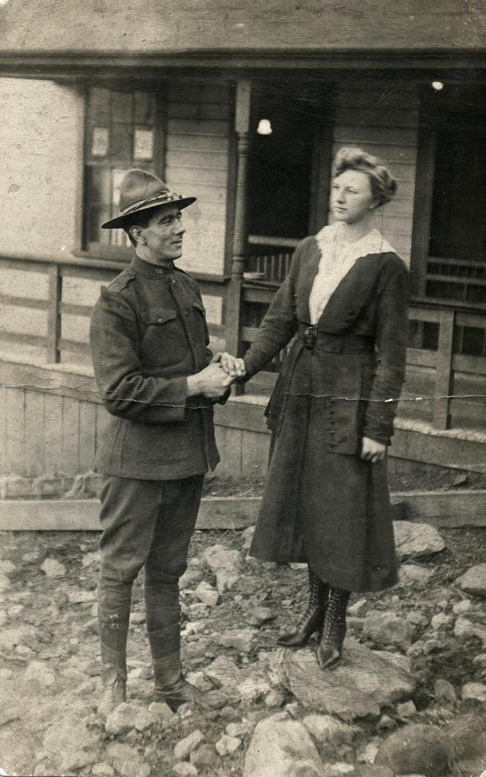 Exterior of man in WWI uniform holding woman's hand