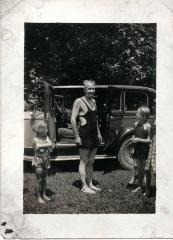 Man and children in front of car
