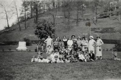 Group of adults and children posing for photo in park