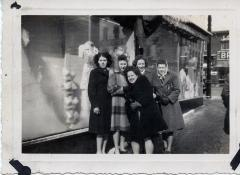 Group of women posing for photo in front of store windows