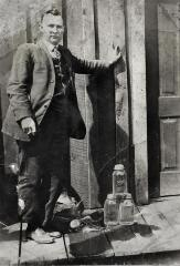 Man standing outside building with moonshine at his feet
