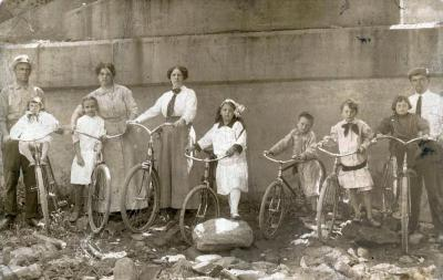 Group of children and adults standing next to bicycles