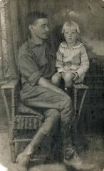 Man sharing a chair with his young son