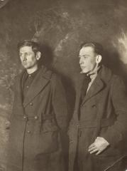 Two men in coats posing for a photo