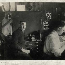 Two men sitting in a watch repair shop