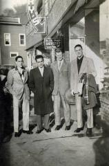 Four men standing in front a building