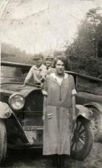 Man, woman, and boy in front of car