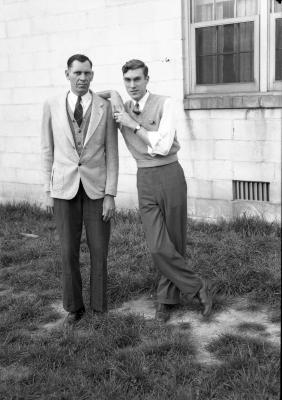 Two men posing in front of a building