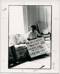 Production still of woman holding protest sign - The Struggle of Coon Branch Mountain