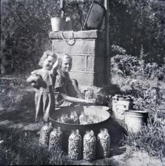 Exterior of woman and daughter canning beans, smiling at camera