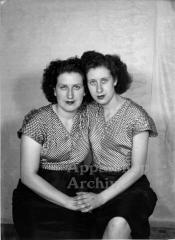 Studio portrait of 2 women in matching outfits