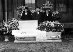 Three people standing with an open casket