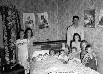 Woman in bed holding 2 infants, surrounded by her husband and children