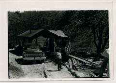 Production still of standing in front of rural house - The Struggle of Coon Branch Mountain