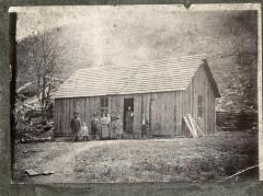 Group of people in front of wooden house