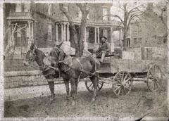 Man driving horse-drawn cart down main street