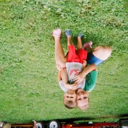 Girl hugging a young boy on lawn