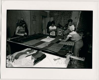 Production still of women and a man working around quilting frame - Millstone Sewing Center