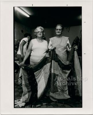 Production still of two women holding quilt - Millstone Sewing Center